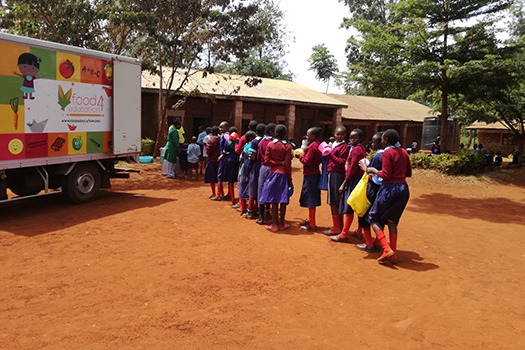Students of Ngewe Primary School line up for Lunch at the recently launched School feeding progam by Tatu City